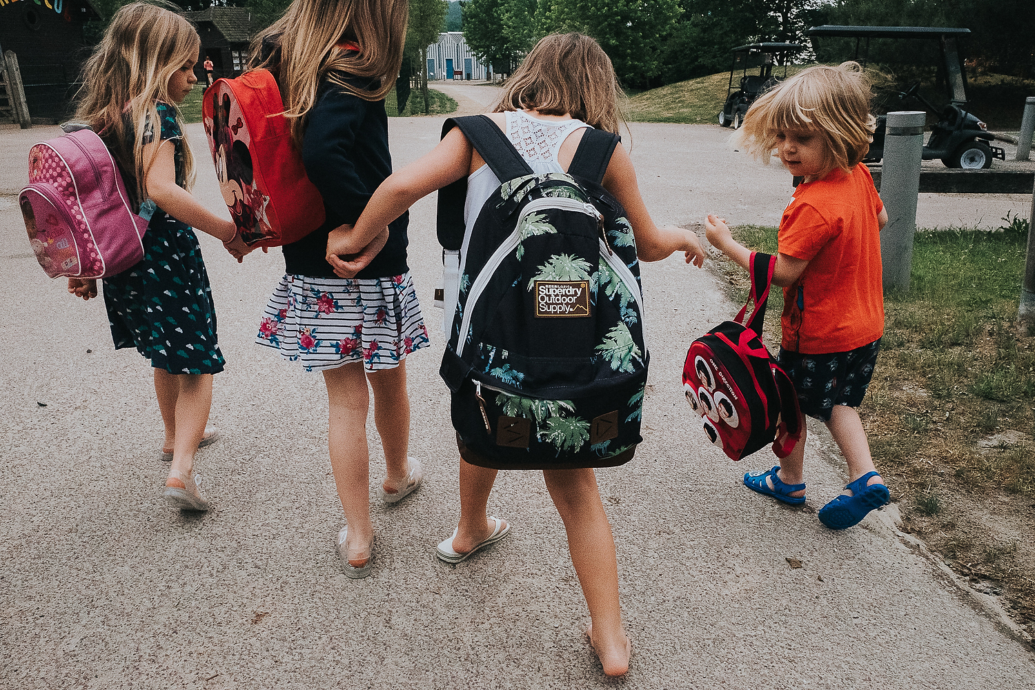 GROUP OF CHILDREN WALKING HAND IN HAND FROM BEHIND WITH RUCKSACKS FAMILY PHOTOGRAPHY AT CENTER PARCS FRANCE LAC D'AILETTE