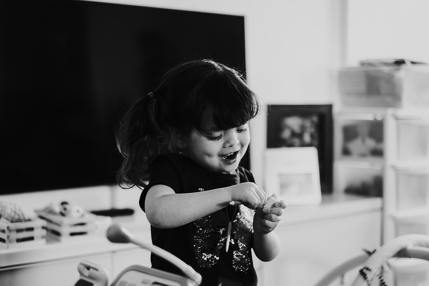 home scene of little girl playing with make believe toys islington family photographer shoot black and white image