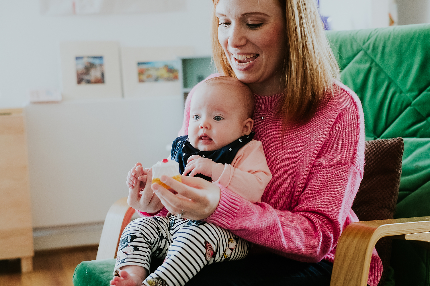 home scene of mother with baby on lap holding pretend piece of cake playing with make believe toys islington family photographer shoot