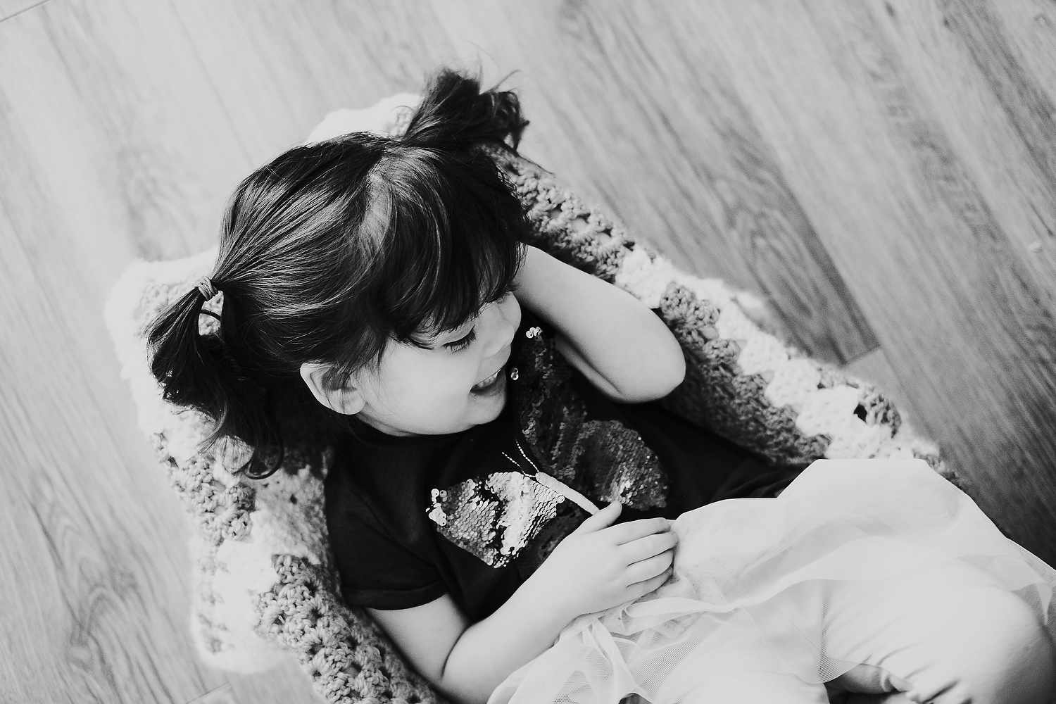 home scene of little girl playing with blanket on the floor islington family photographer shoot black and white