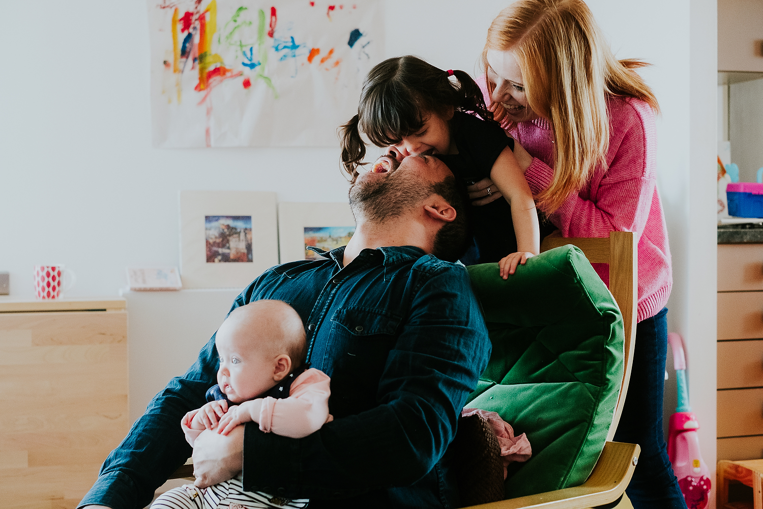 mother and father playing with baby girl and toddler daughter on chair at home islington family photographer
