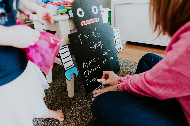 close up mum writing on blackboard for child's make believe play shop islington family photographer