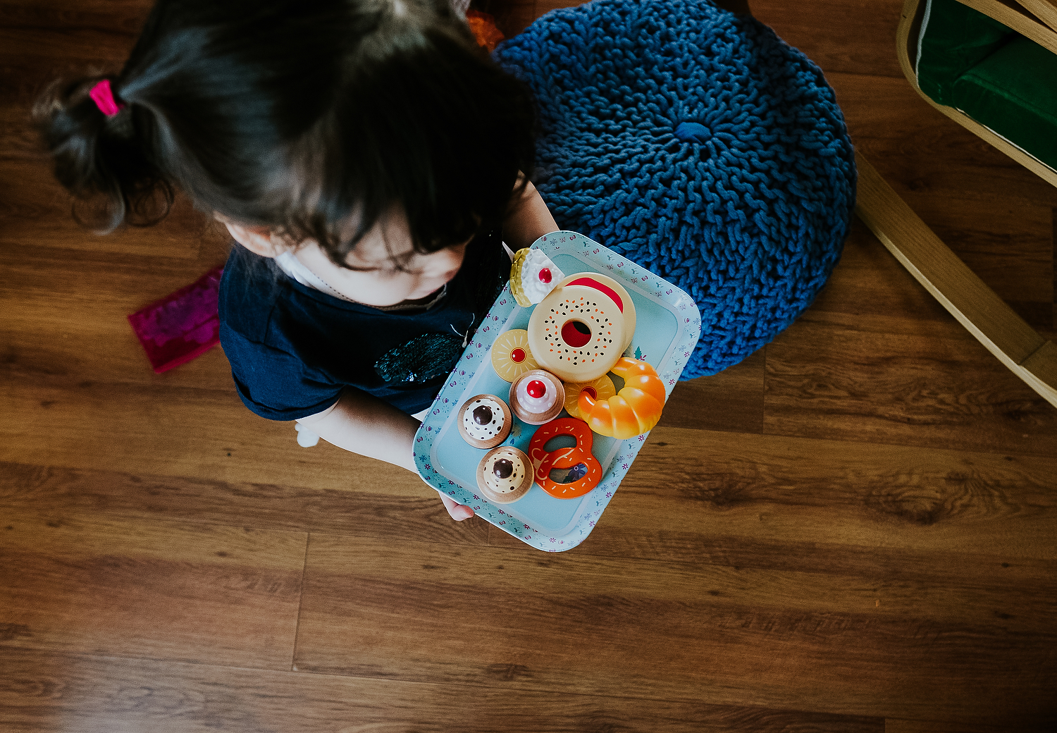 aerial shot of toddler girl carrying toy tray with pretend cakes islington family photographer
