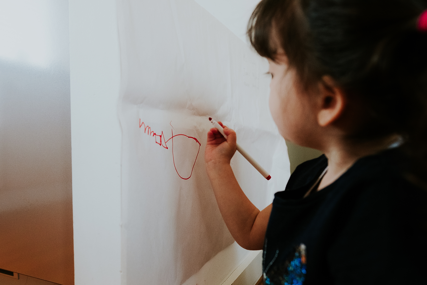 islington family photographer close up shot of toddler girl drawing with red pen on papered wall at home