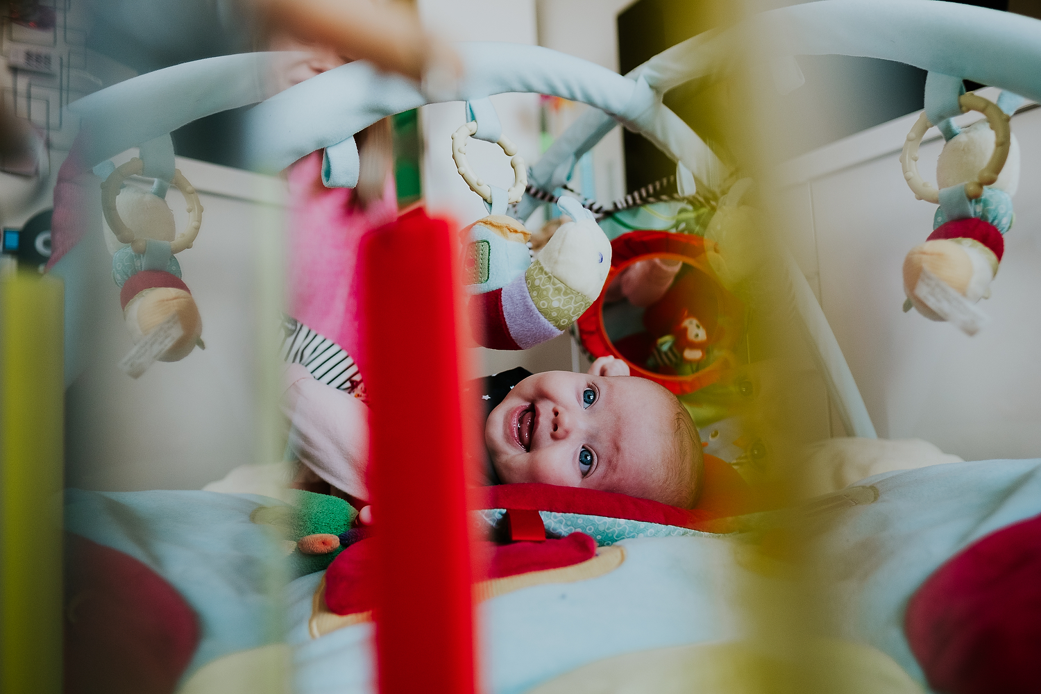 islington family photographer shot of baby lying on colourful play mat smiling