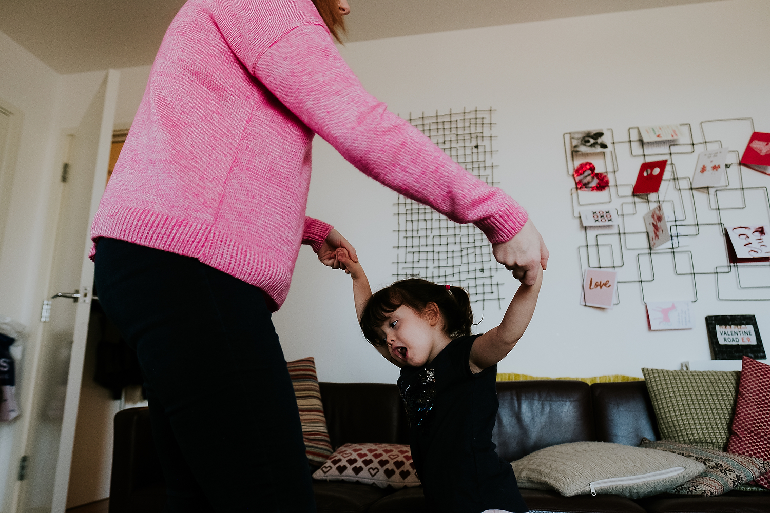 islington family photographer mother and toddler daughter dancing in living room at home