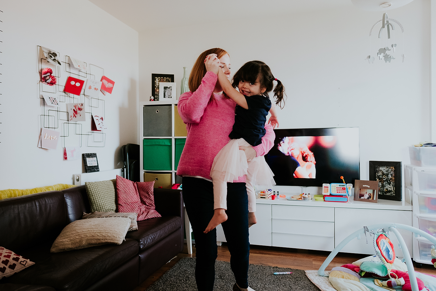 islington family photographer mother and toddler daughter dancing in living room at home with dirty dancing movie on tv in background