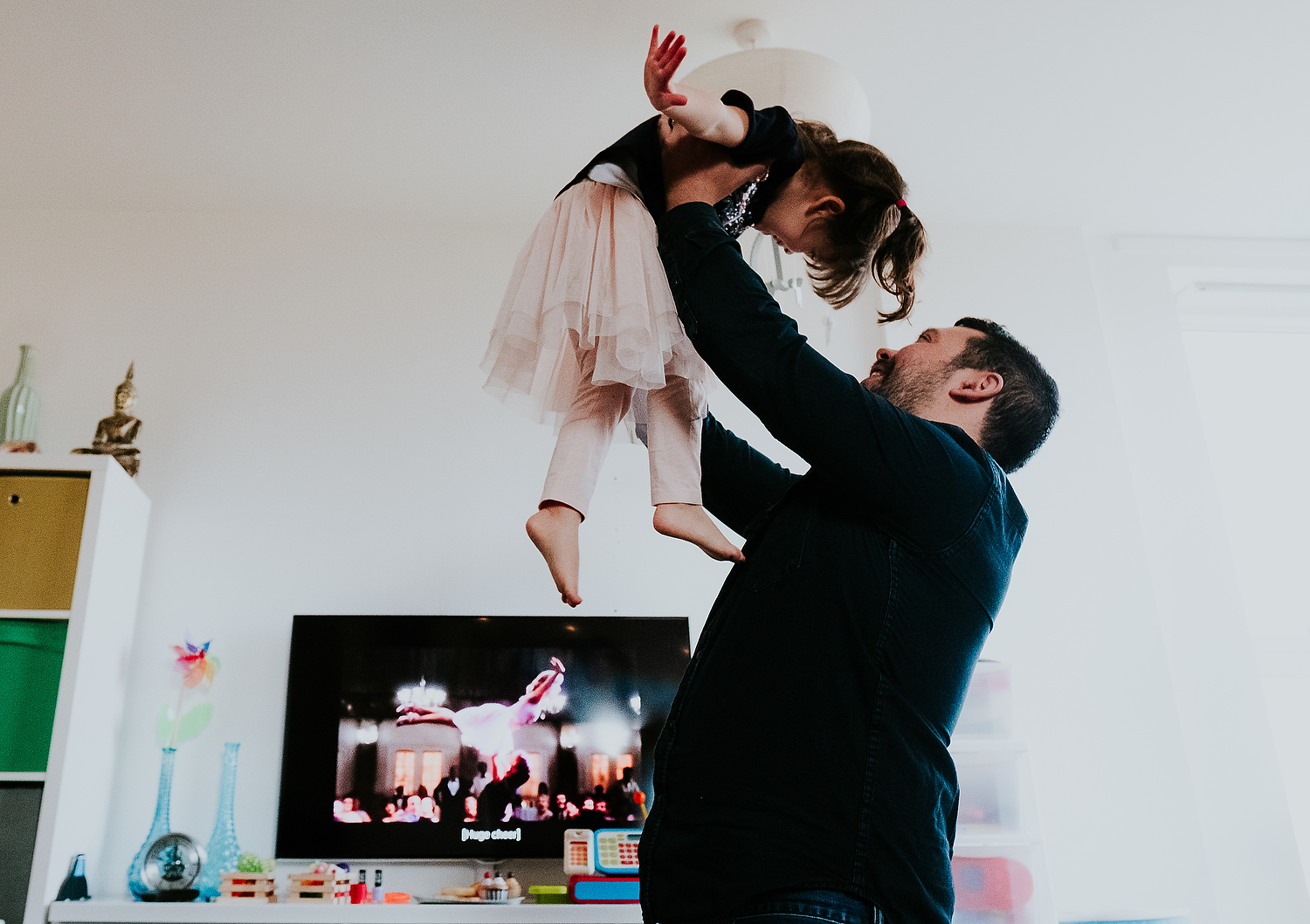 islington family photographer dad and toddler daughter dancing in living room at home with dirty dancing movie on tv in background