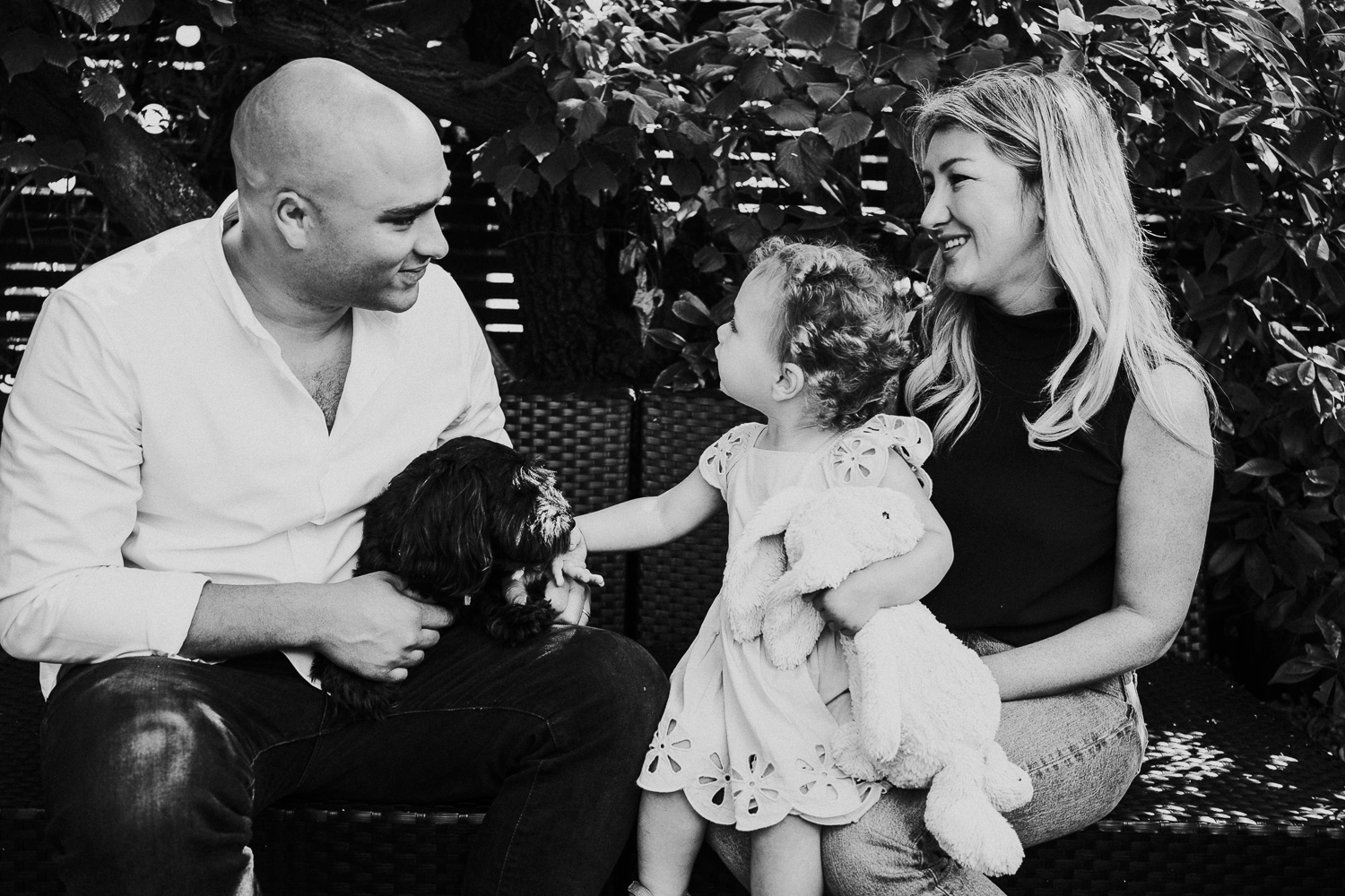 NORTH KENSINGTON FAMILY PHOTO SESSION black and white shot of family and dog sitting on sofa in garden