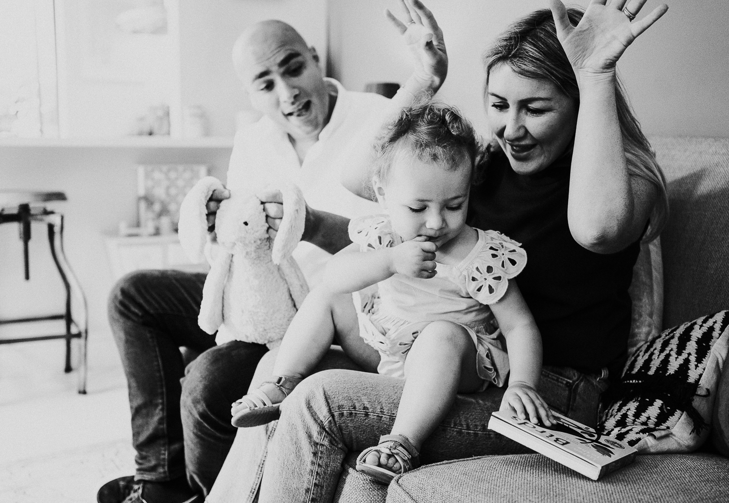 north kensington family photo session parents reading book with daughter toddler on sofa