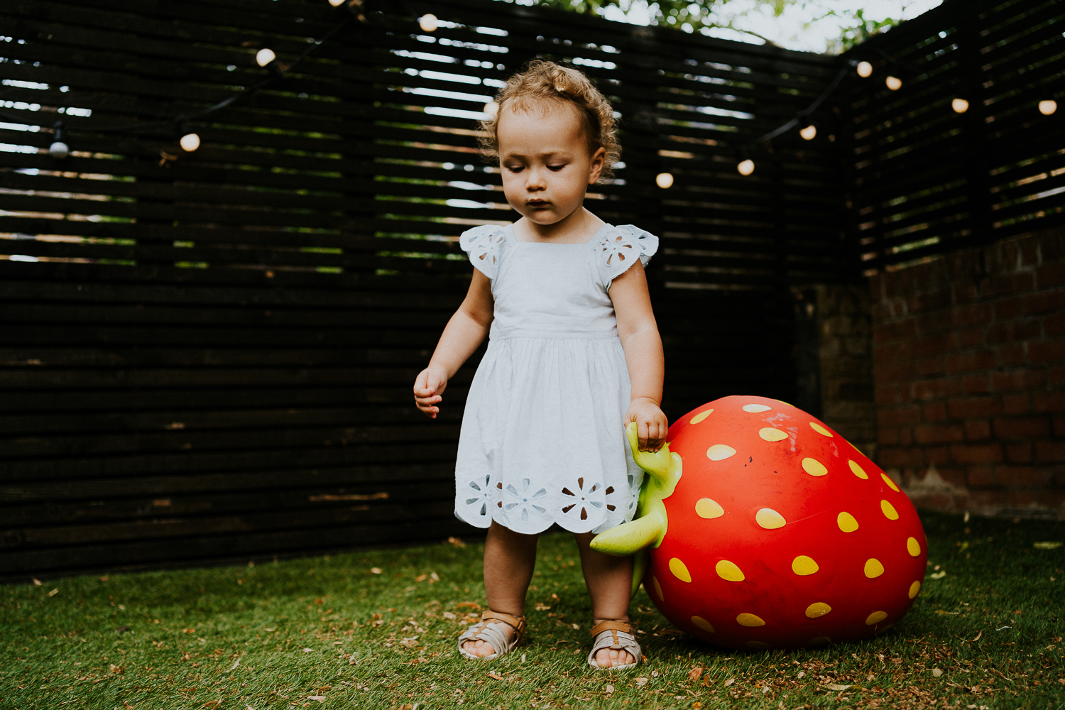 toddler girl playing with giant strawberry toy in garden NORTH KENSINGTON FAMILY PHOTO SESSION