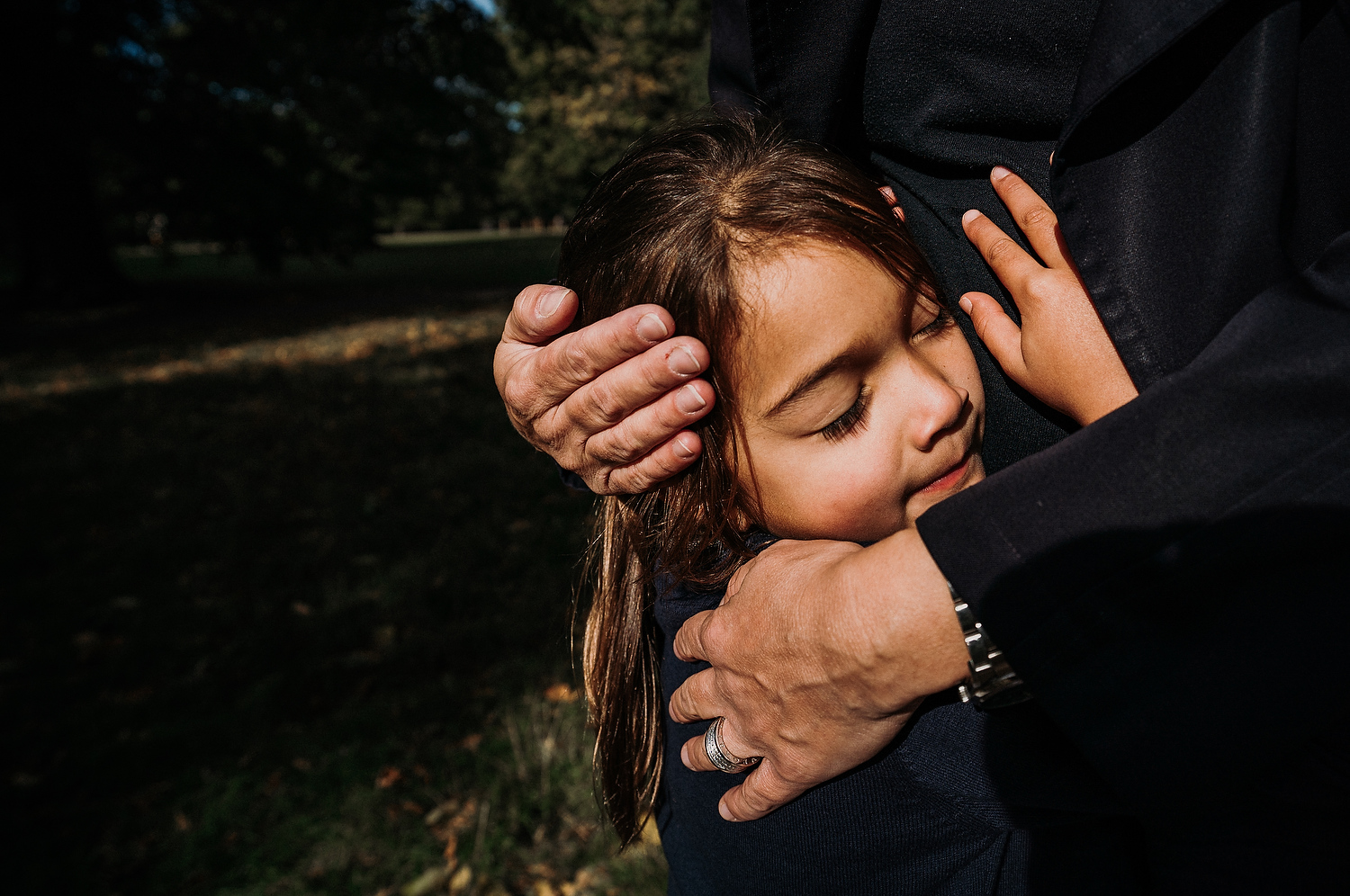 BOOKING A FAMILY PHOTO SESSION CLOSE UP CHILD'S DAUGHTER HEAD BEING HELD IN EMBRACE BY MOTHER