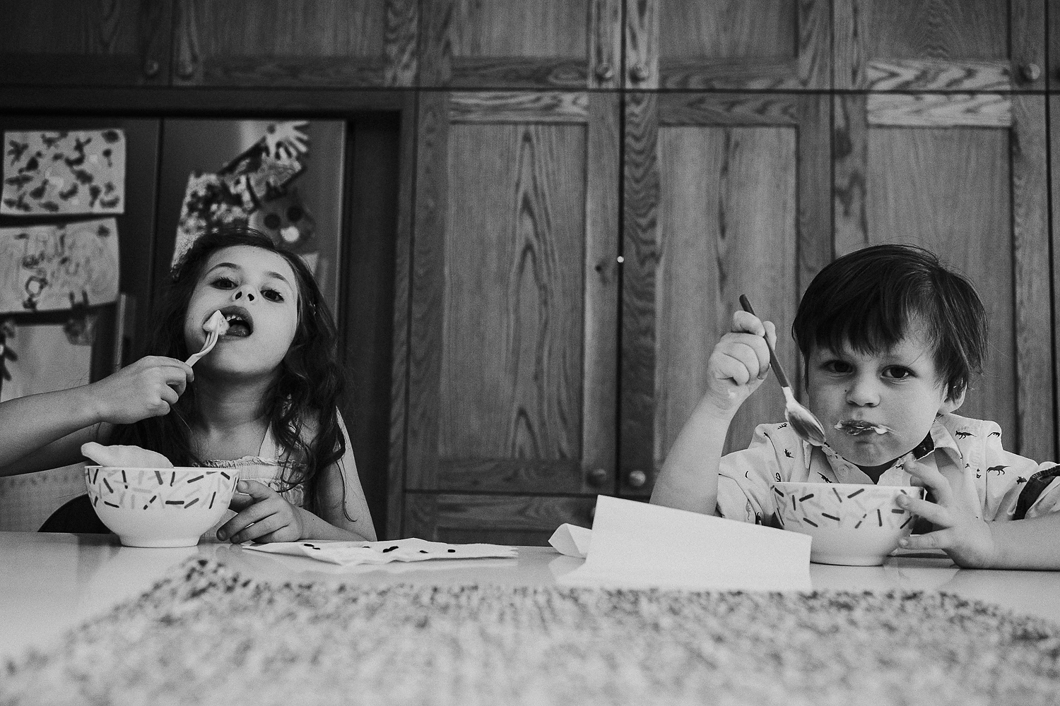 BOOKING A FAMILY PHOTO SESSION BROTHER AND SISTER CHILDREN EATING FOOD FROM A BOWL AT KITCHEN COUNTER