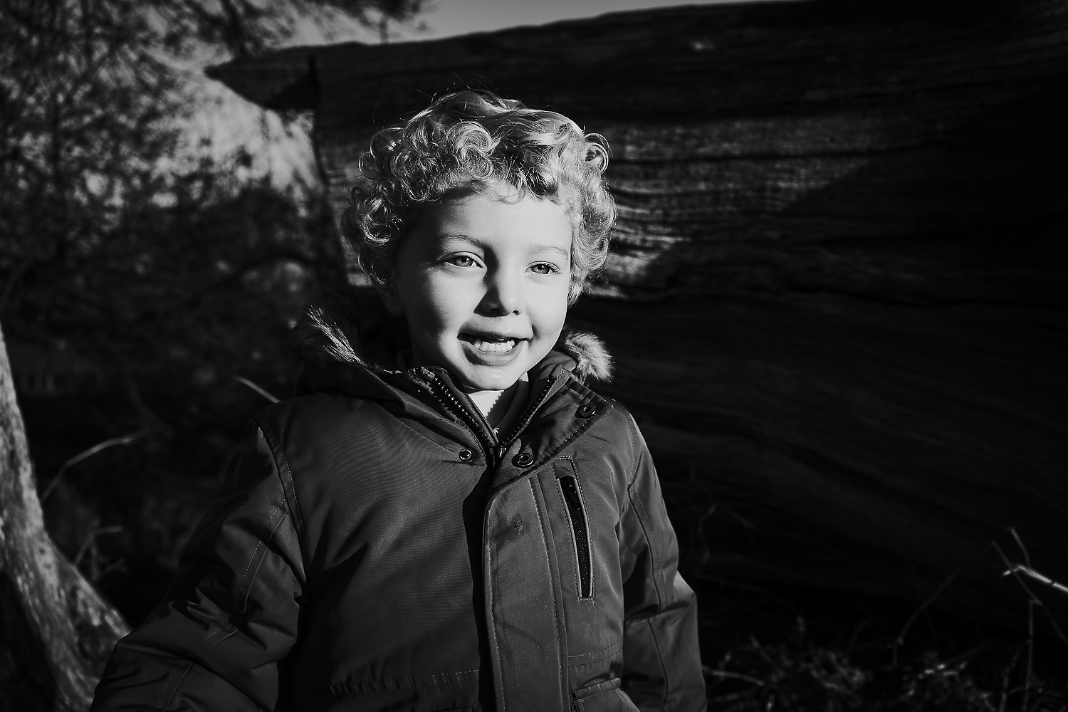 BOOKING A FAMILY PHOTO SESSION BLACK AND WHITE SHOT OF LITTLE BOY WITH CURLY HAIR
