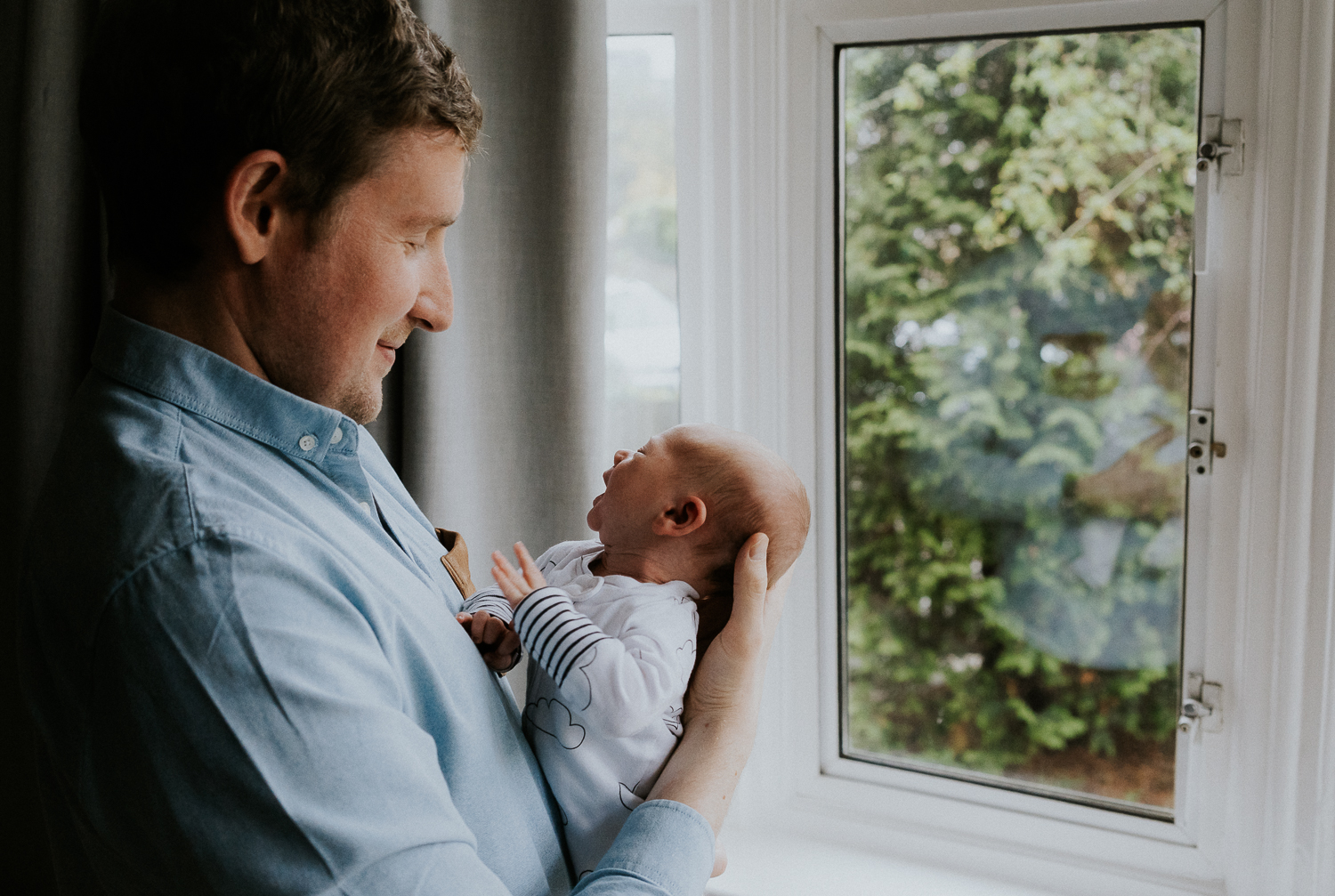 newborn photo session at home in highgate photo of baby boy with father