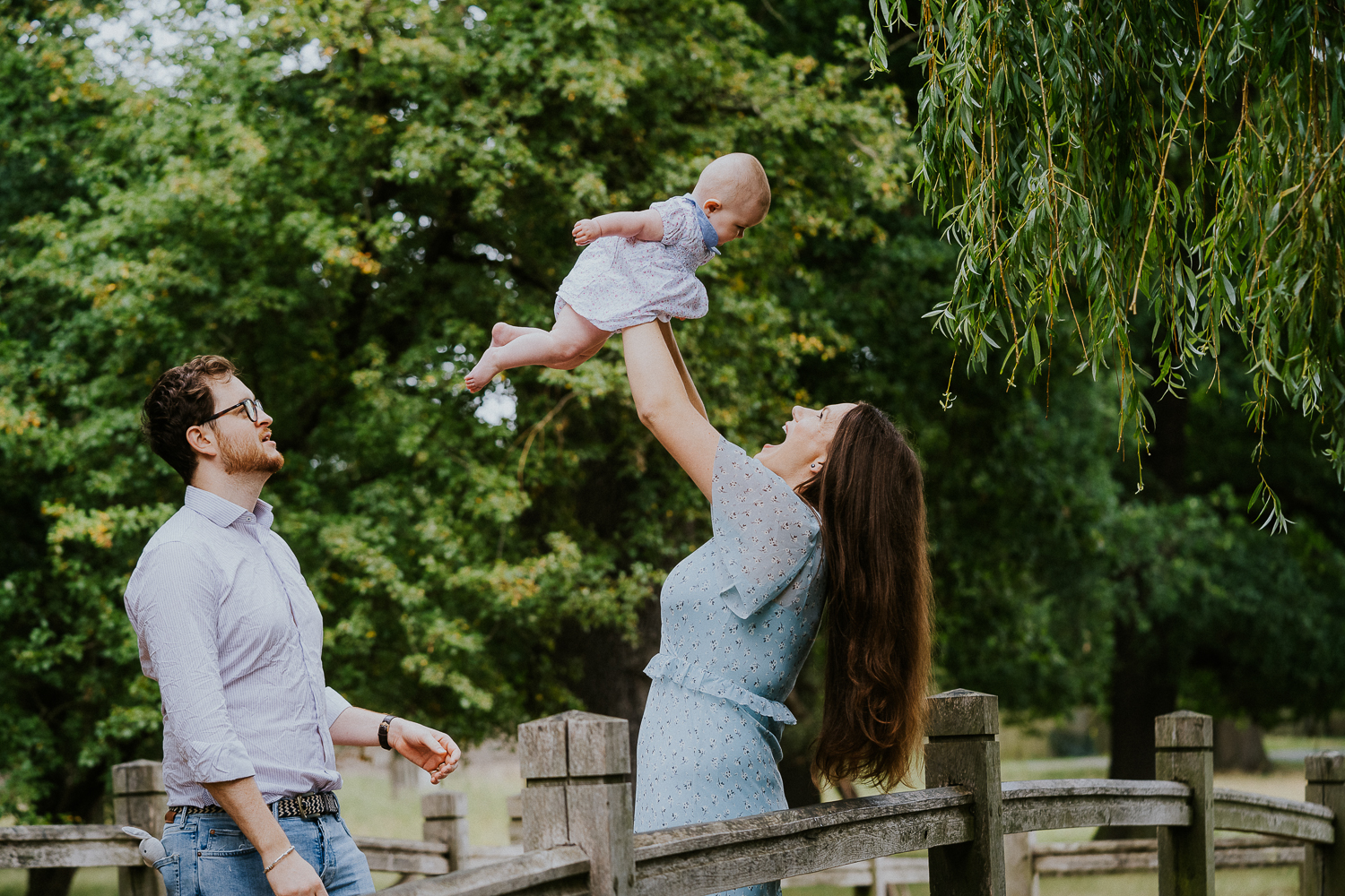 SPRING MINI PHOTO SESSIONS FAMILY ON BRIDGE IN RICHMOND PARK IN SUMMER HOLDING BABY IN AIR