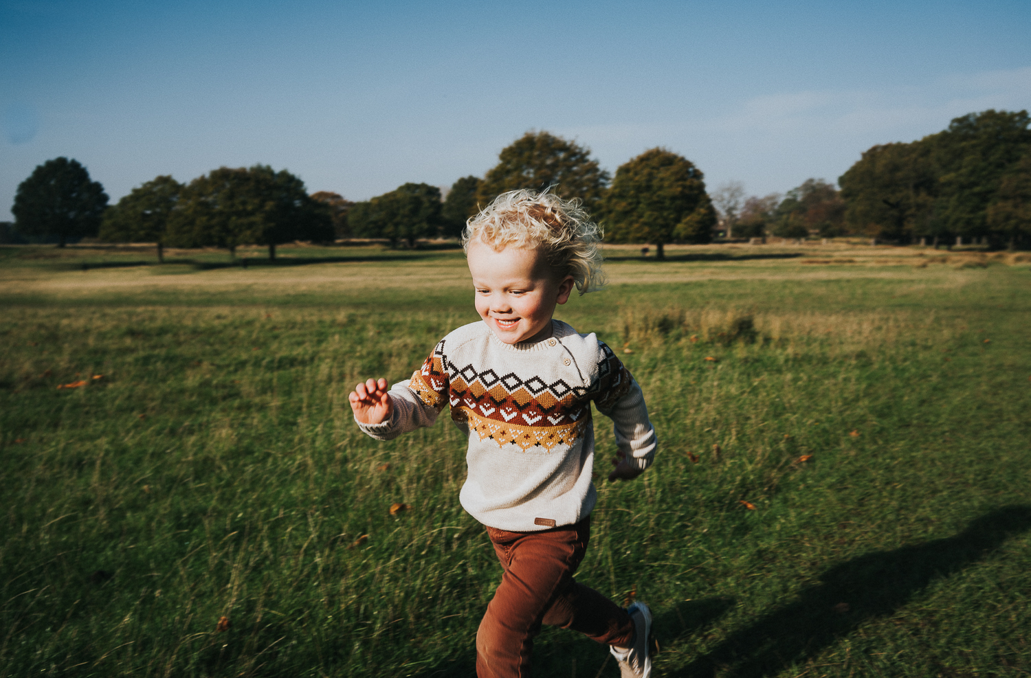 SPRING MINI PHOTO SESSIONS LITTLE BOY WITH BLONDE CURLS RUNNING AND SMILING IN RICHMOND PARK LONDON