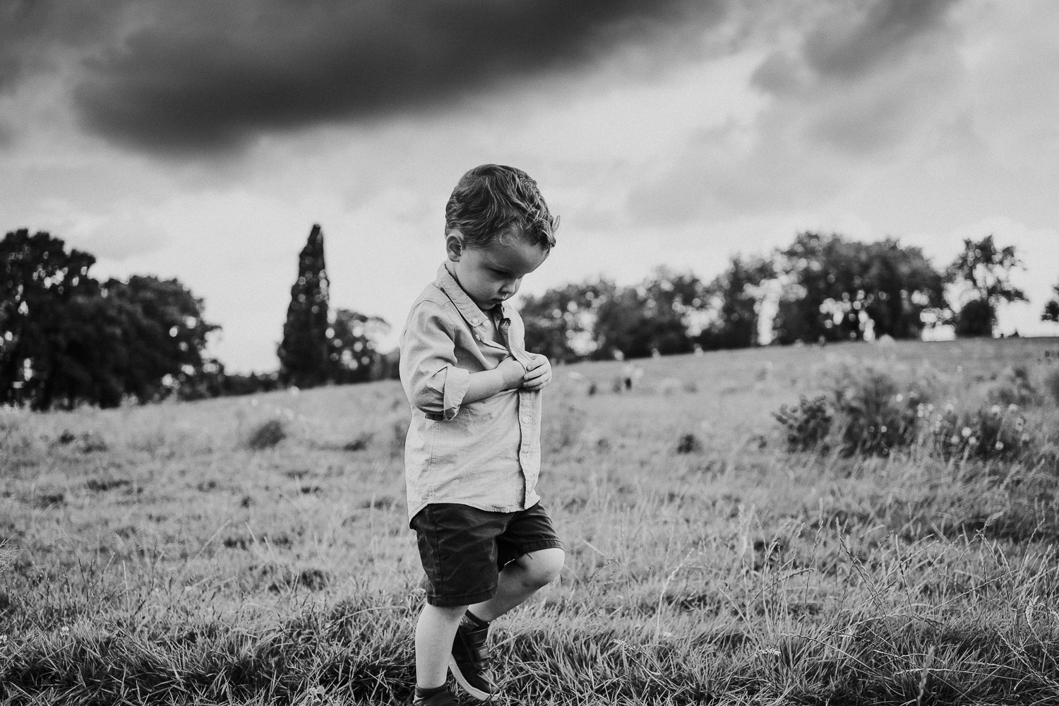 SPRING MINI PHOTO SESSIONS BOY WALKING IN GLADSTONE PARK WITH STORMY SKY BLACK AND WHITE
